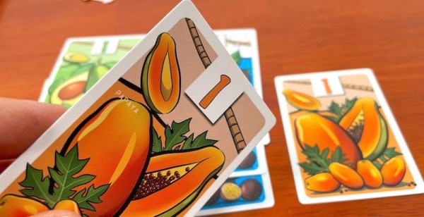 A hand holds a papaya card from Fruit Passion