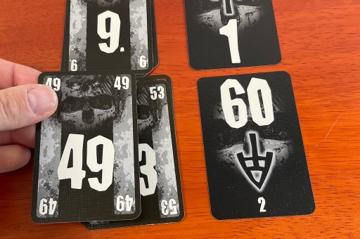 Hand holding card 49 over card 43. To the right, a card that has a large 60 and an arrow pointing down to a small 2.