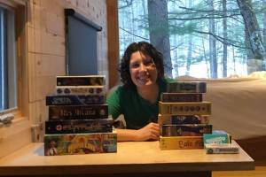A woman sitting behind two stacks of games.