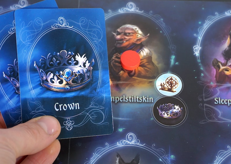 Red marker on Rumplestiltskin. Hand holding two Crown Artifact cards.