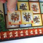 Gunkimono tile: orange and yellow, being placed over brown and blue tiles on the board