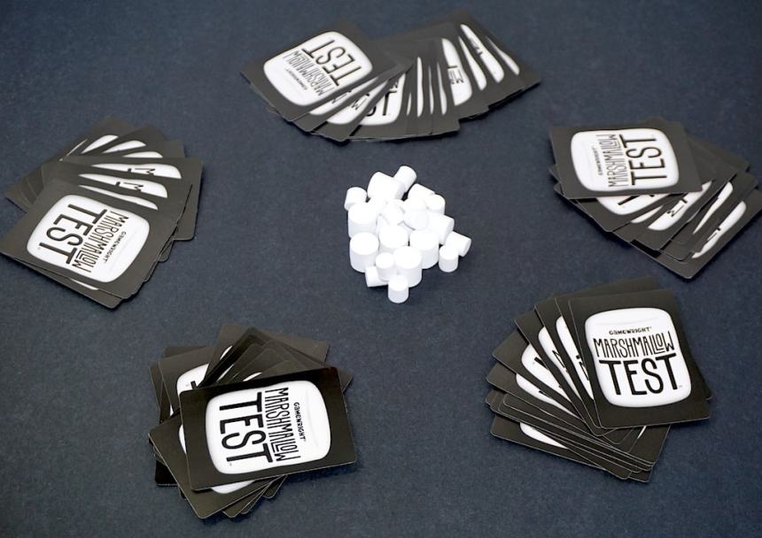 five hands of cards, each face down around a central pile of marshmallows