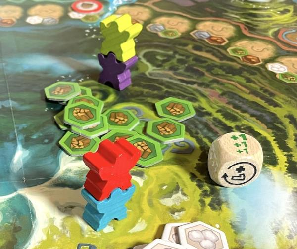 Die shows green +1s. Yellow and purple meeples stacked in the background, blue and red meeples stacked in the foreground.