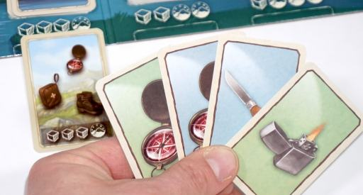 hand of cards showing two compasses, knife, and lighter. Hike card in background with compass, first aid kit, boots.