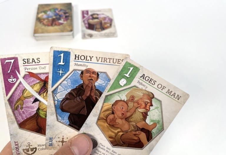A hand of cards: 7 Seas, 1 Holy Virtues, 1 Ages of Man. Blurred in the background is the Quatorze deck and a single face up card.