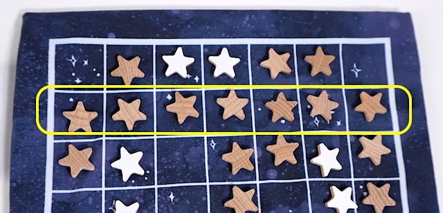 A line of dark (natural wood) star tokens
