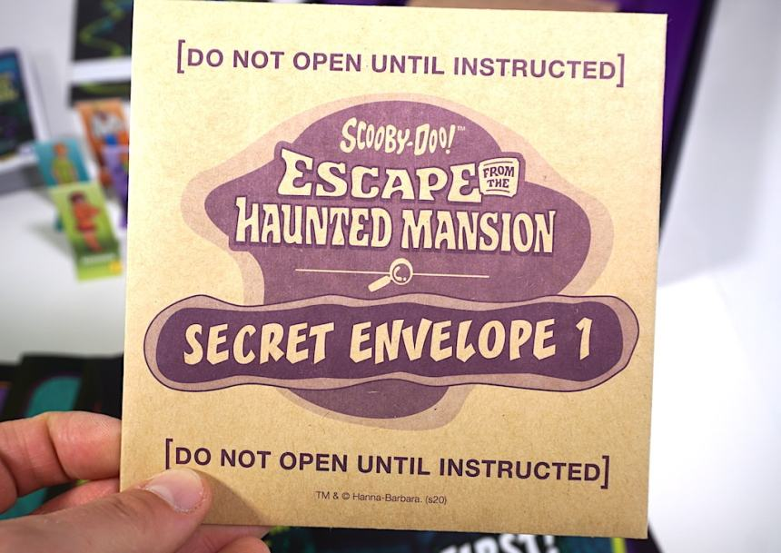 Hand holding an envelope - Scooby Doo Escape the Haunted Mansion: Secret Envelope 1 - Do not open until instructed