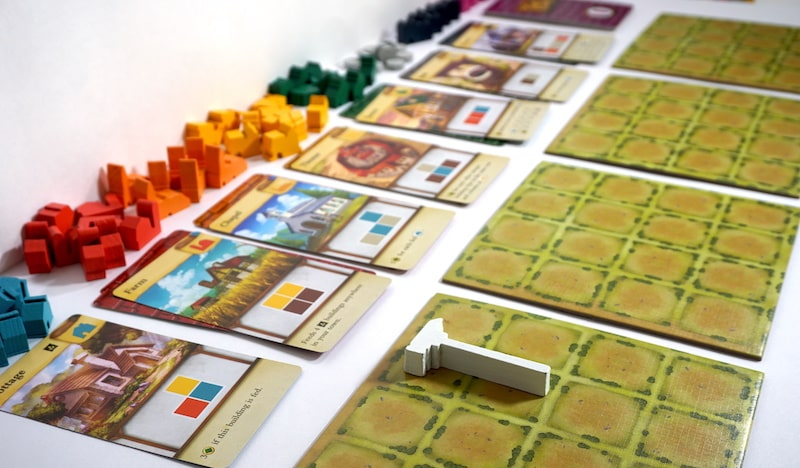 4 player boards and a row of cards with corresponding wooden buildings: cottage, farm, chapel, theater, tavern, etc.