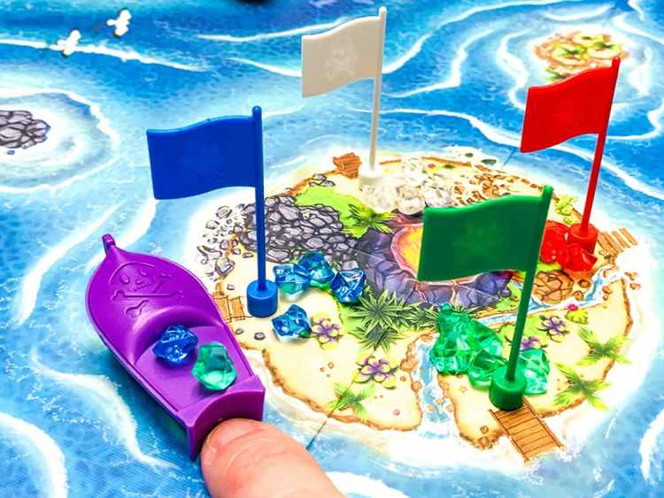 finger pushing a plastic boat holding two gems