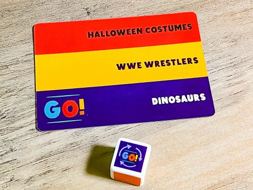 Above, card with the topics: Halloween costumes; WWE wrestlers; GO! Dinosaurs. Below, die showing GO!
