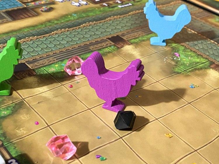A purple chicken figure next to a black gem