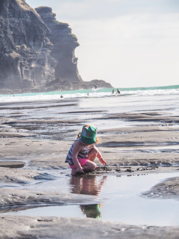 young girl playing in the tide pools at Piha beach, North Island, New Zealand with kids