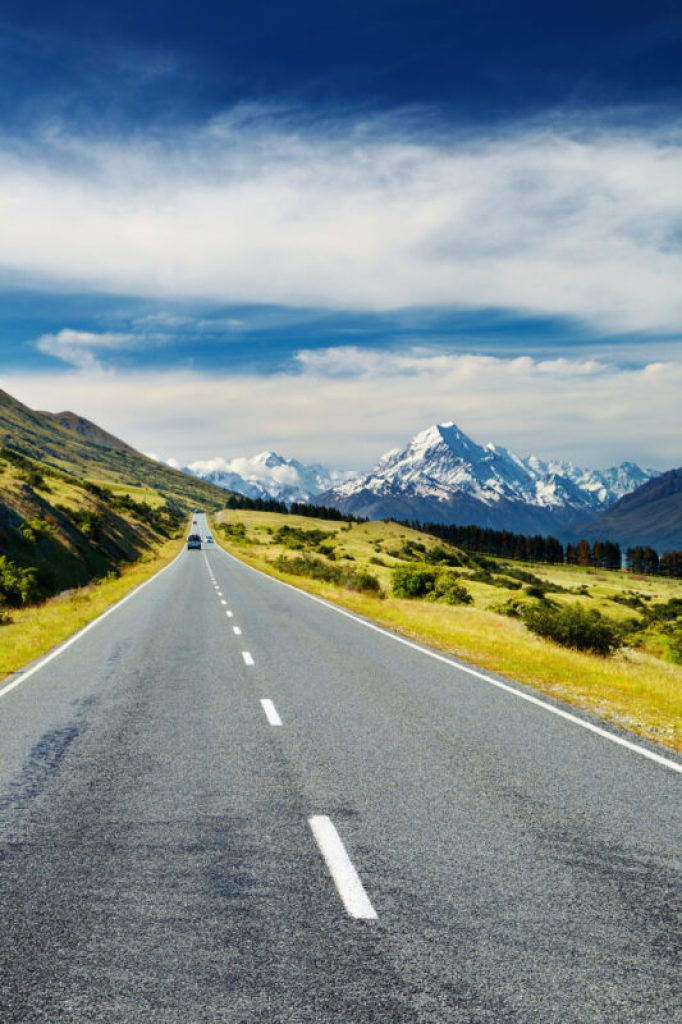 car driving on a long empty road toward Mount Cook, South Island, New Zealand