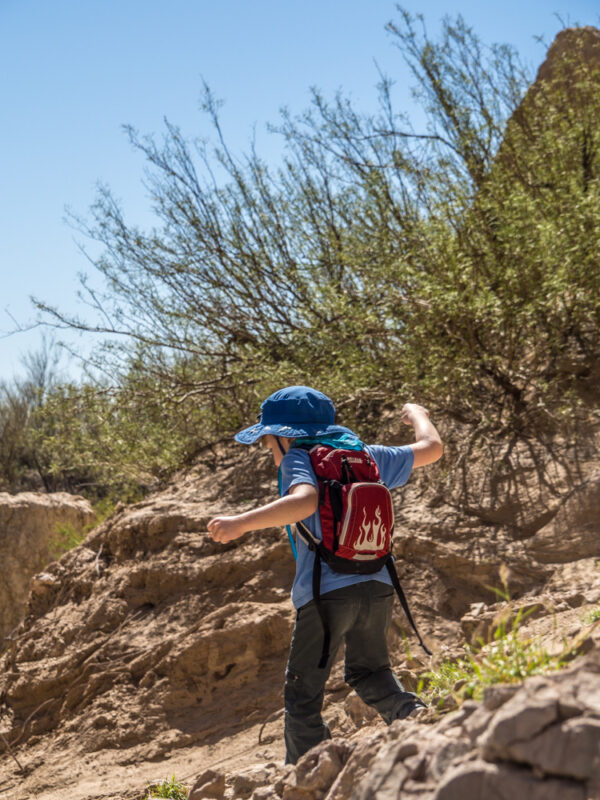 Young boy with red backpack and blue hat hiking in Big Bend National Park, Texas