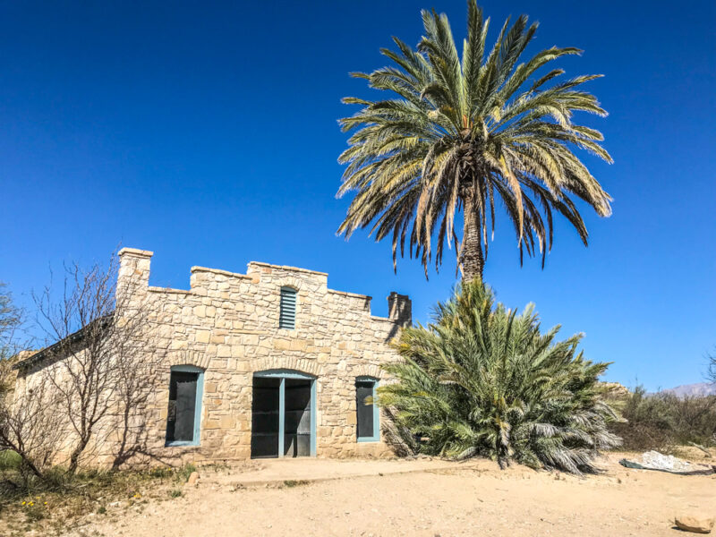 Old stone building with palm tree in front, original Big Bend hot springs hotel in Big Bend National Park, Texas