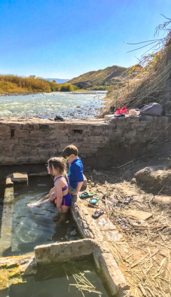 Two children sitting in the tub at Big Bend National Park hot springs along the Rio Grande River in Texas