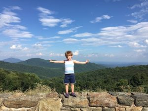 young boy standing on a rock wall along Skyline Drive in Shenandoah National Park with kids; background contains green rolling mountains and blue sky