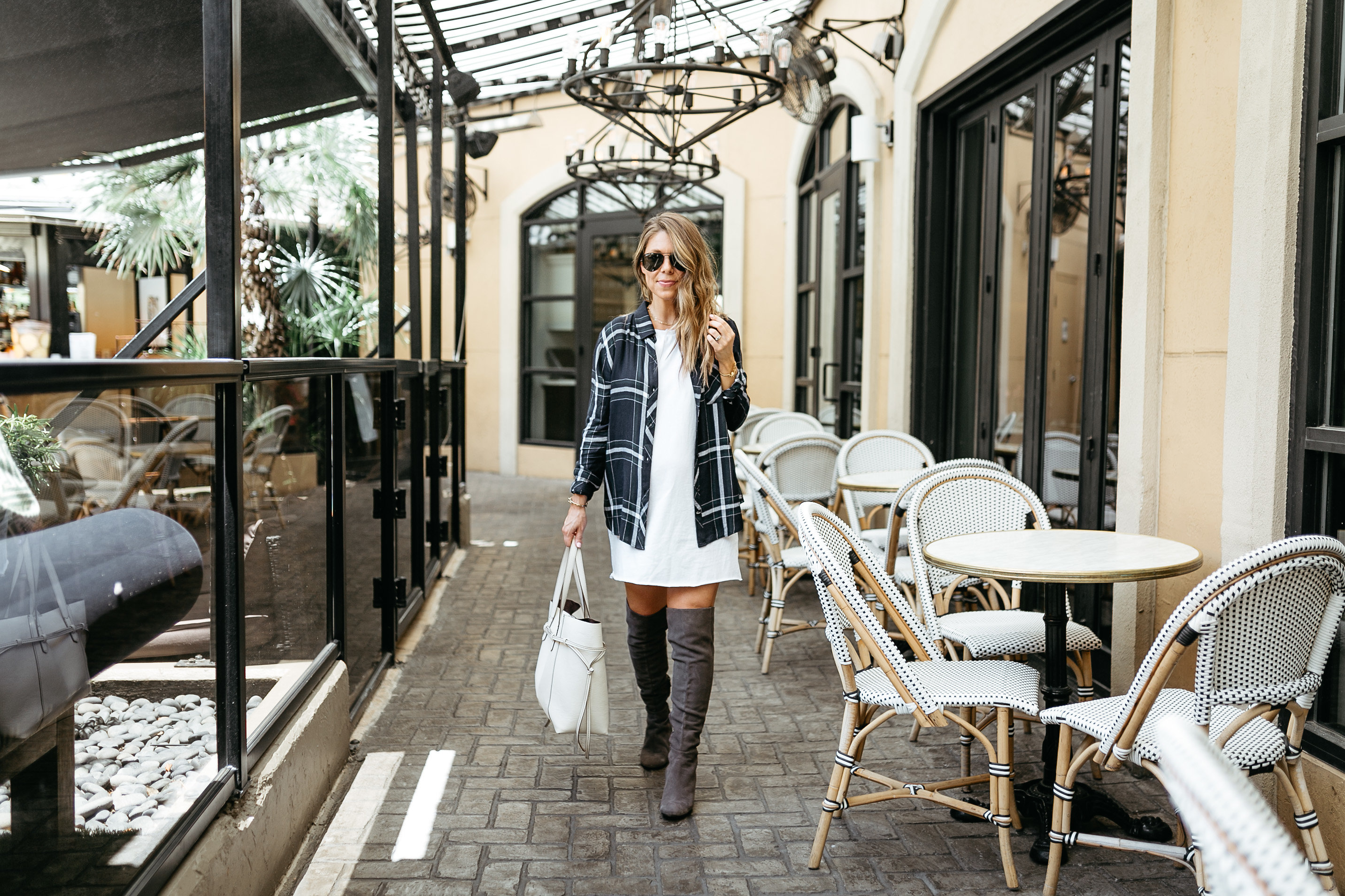 fashion blogger wearing plaid shirt with dress and over the knee boots