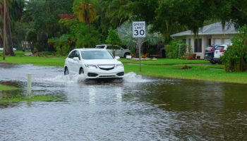 Heavy flooding and storm surge in residential neighborhood with a car driving through deep splashing water in the flooded street in front of houses with Speed Limit sign on side of the road.