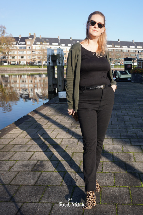 girl standing on the waterside facing the camera, showing her new dawn jeans