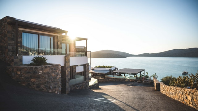 Getting The Most For Your Money In Property - sunrise over beautiful house by water image