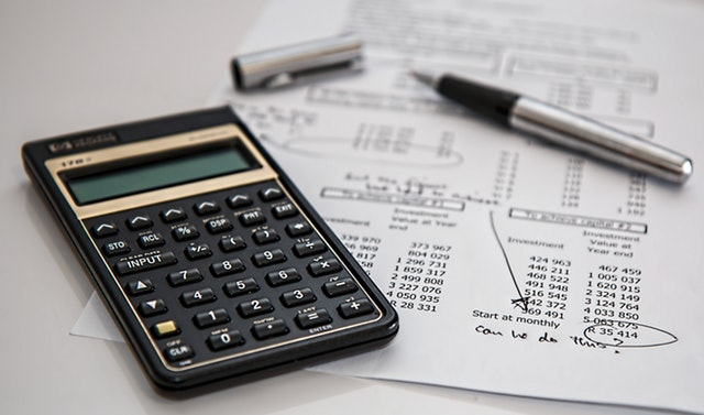 Simple Savings For Solvency - image of calculator, pen and financial calculations