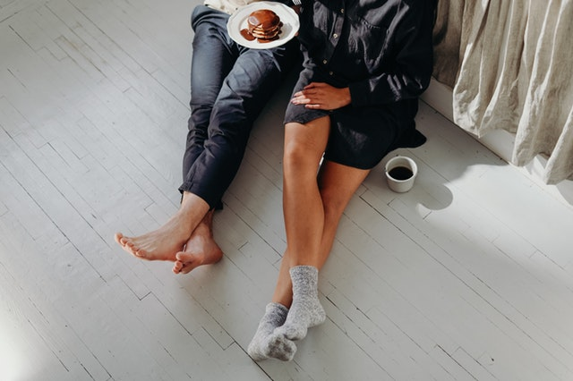 Moving In With Your Partner: Tips and Tricks - couple having breakfast on the floor image