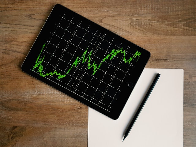 Crypto Volatility Vs. Forex Liquidity – Choose Between the Two to Achieve A Goal of Massive Profits in Trading - tablet on desk with stock, crypto or forex trading screen