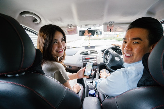 3 Hacks to Owning a Car on a Tight Budget - smiling couple sitting in a car