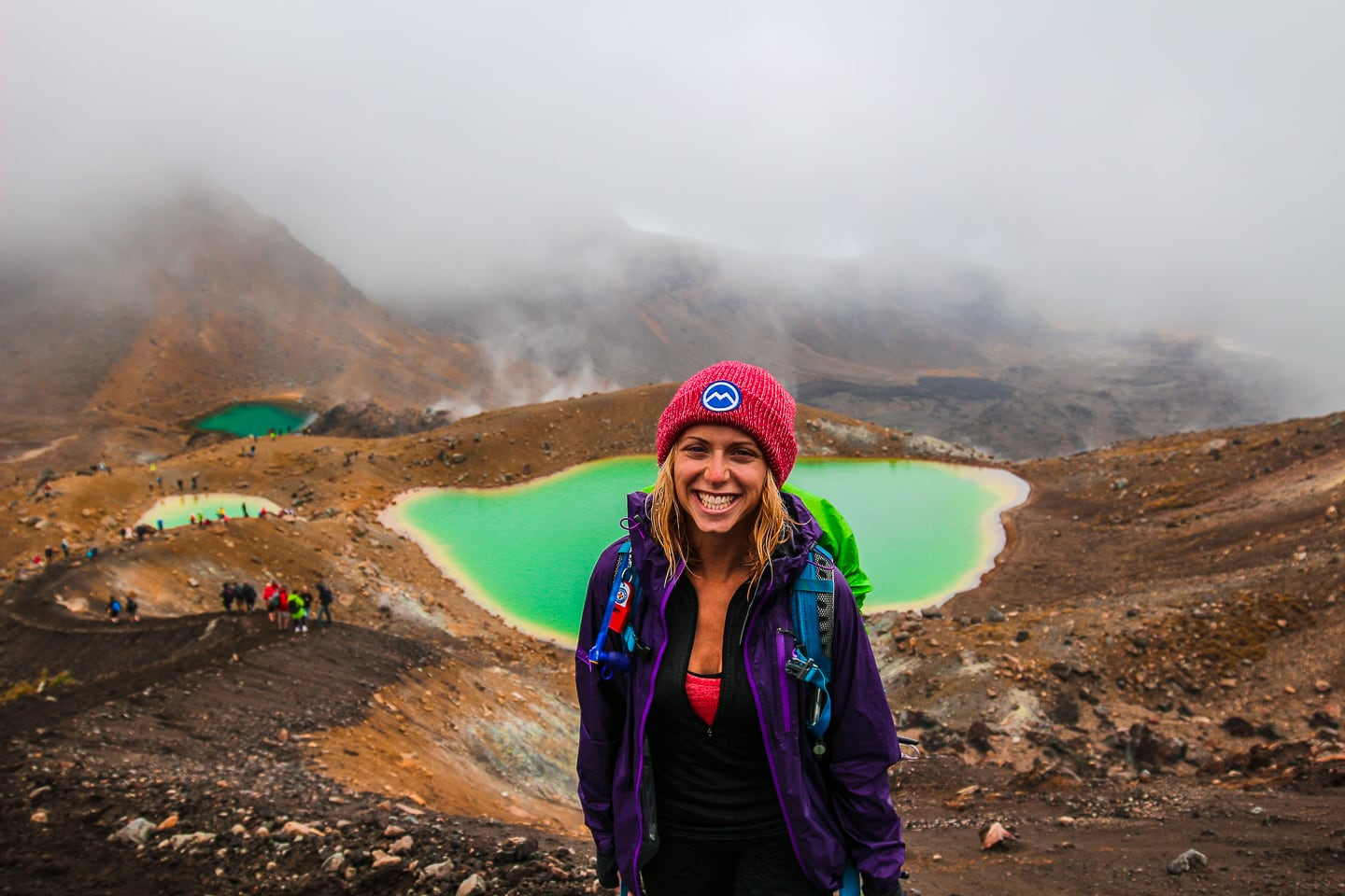girls stands in front of a green lake wearing a purple rain jacket and red beanie; the lake is bright green, but otherwise the landscape is surrounded by fog