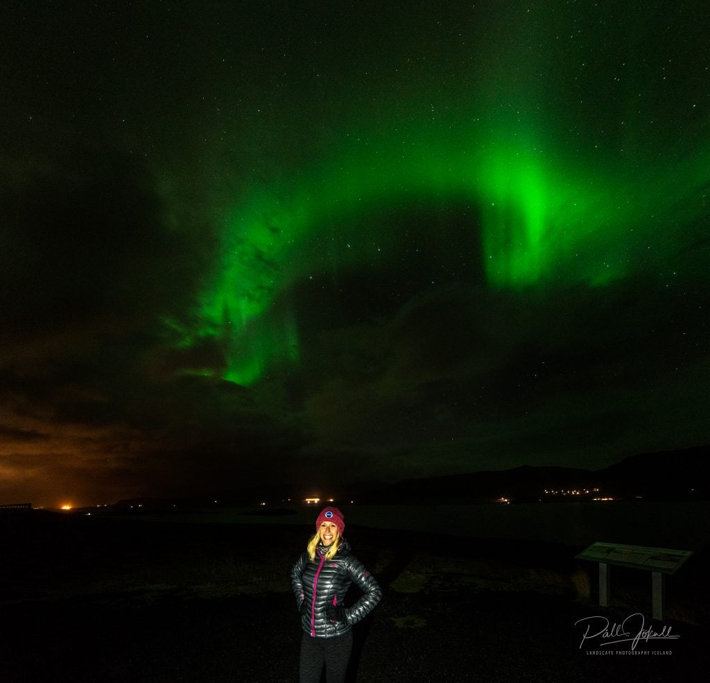 girl stands with northern lights in iceland