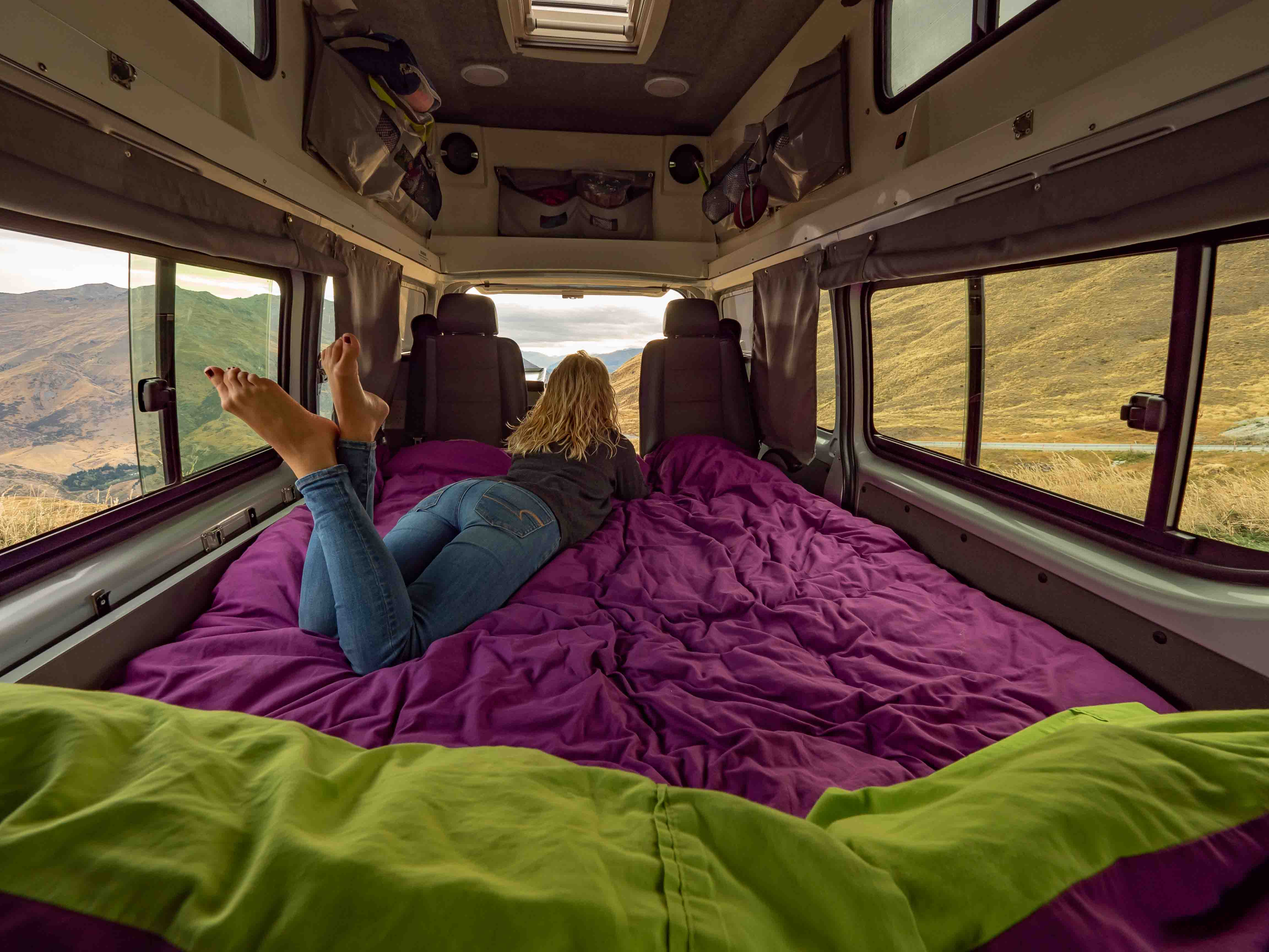girls lays on bed inside a campervan, admiring the view. you can see green pillows in the foreground and a she is laying on a purple duvet.