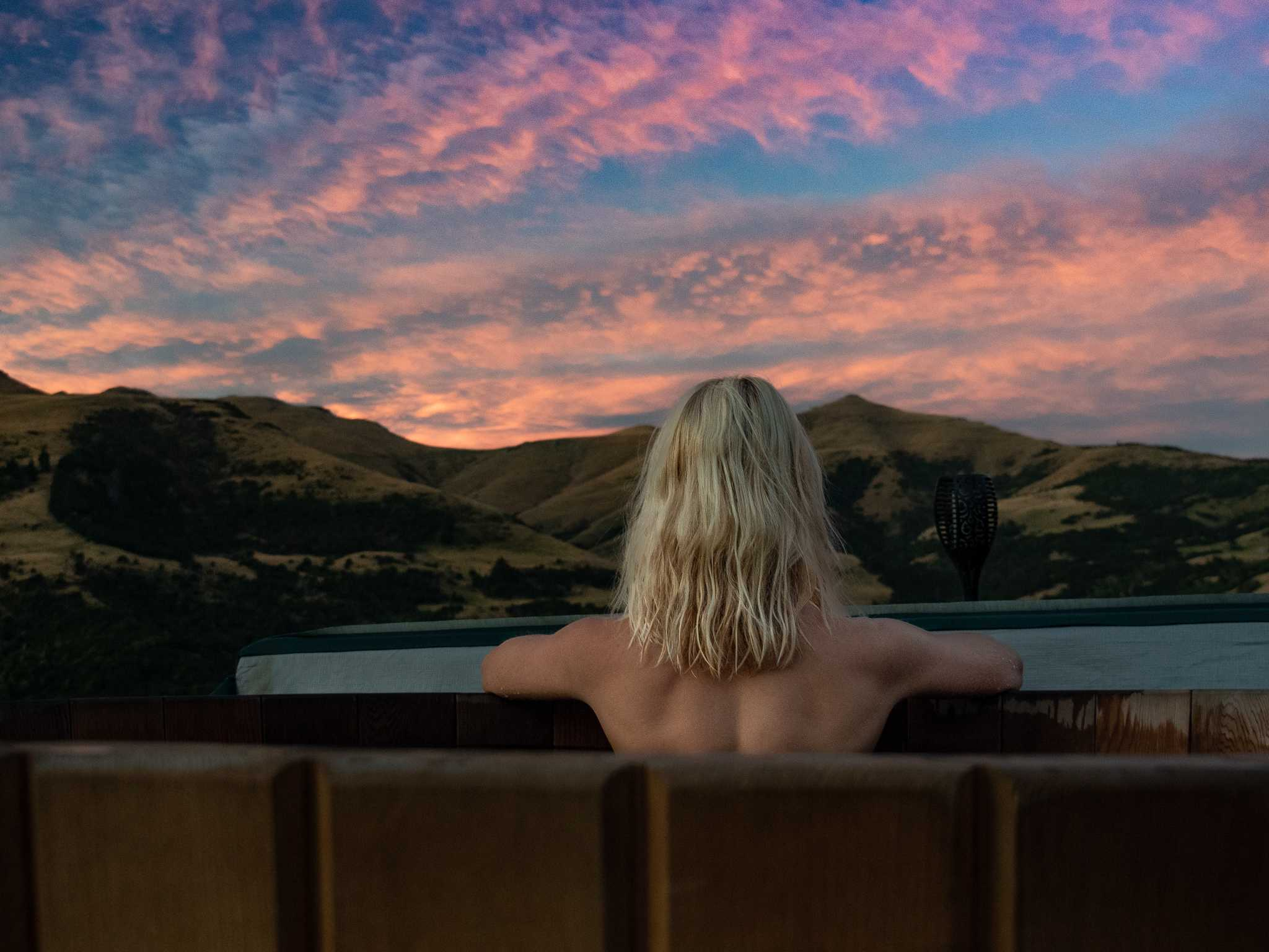 girls sits in hot tub with cotton candy skies