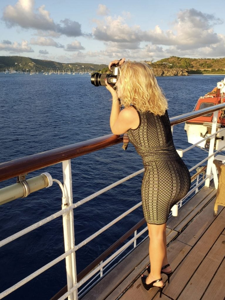 girl leans over side of cruise ship to take a photo