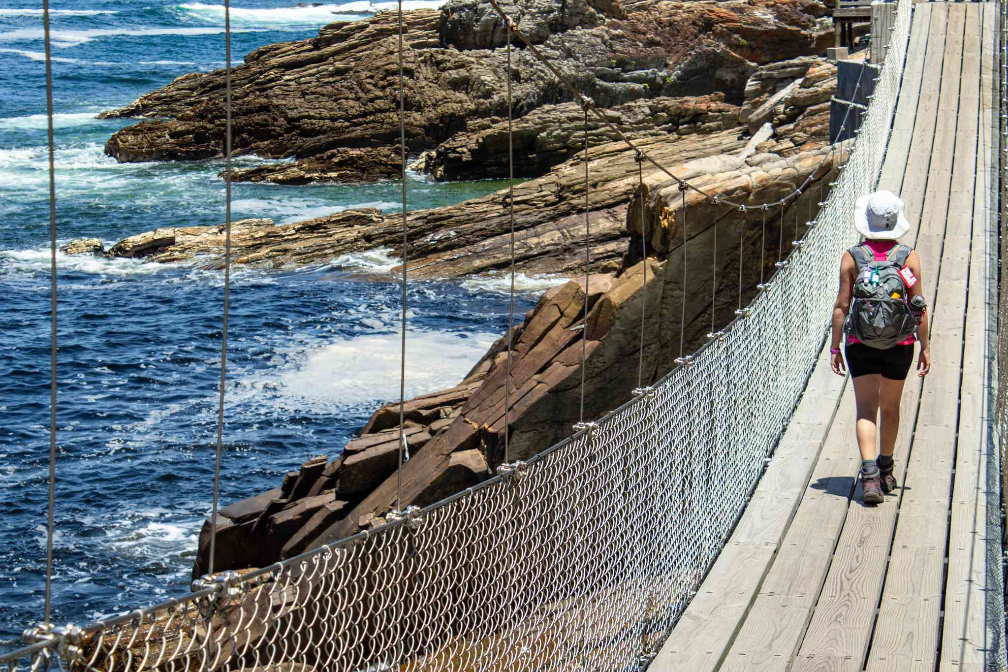 girl walks across suspension bridge with blue water to her left