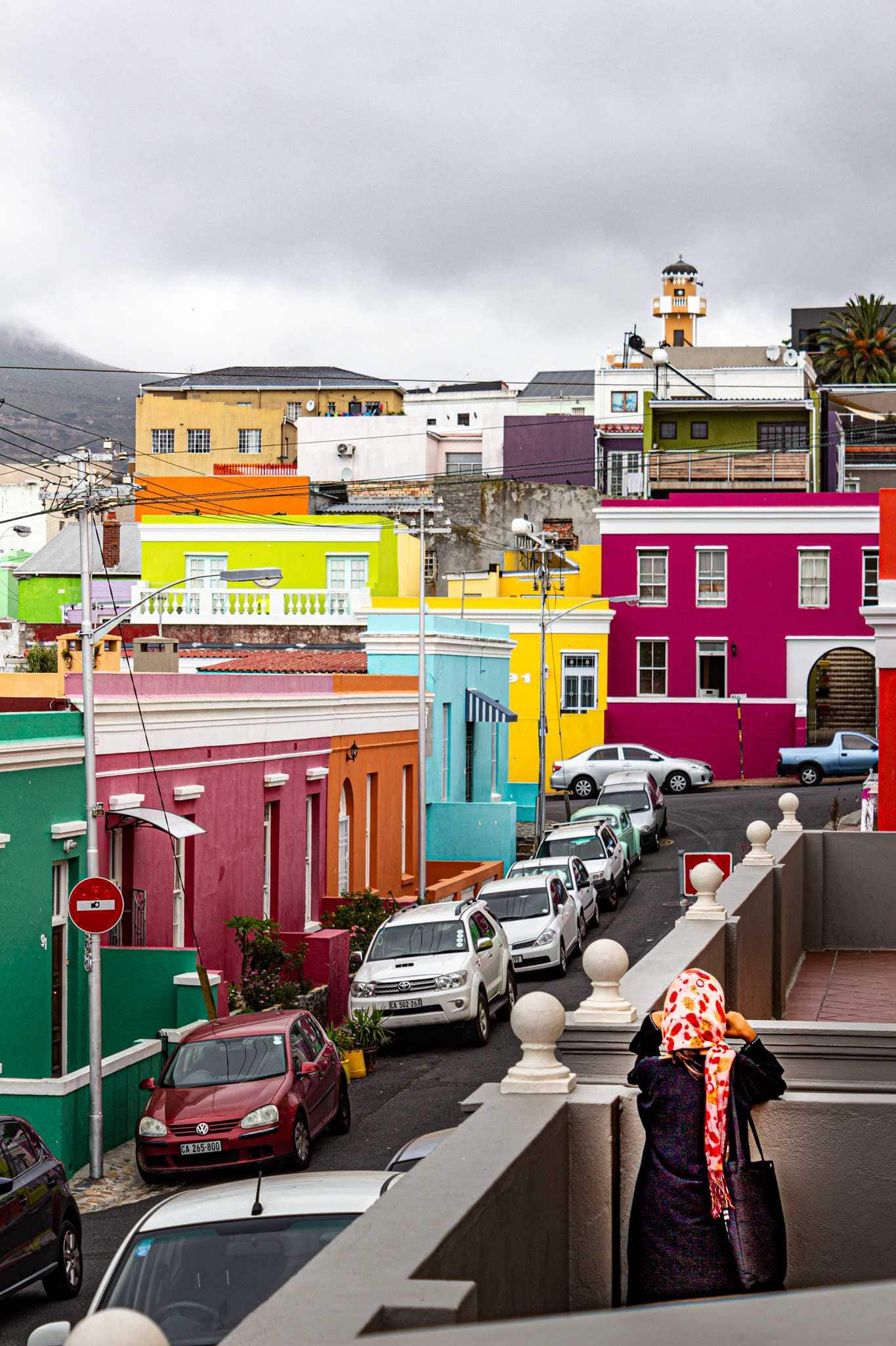 many colorful buildings in bo-kaap and a woman looking at them