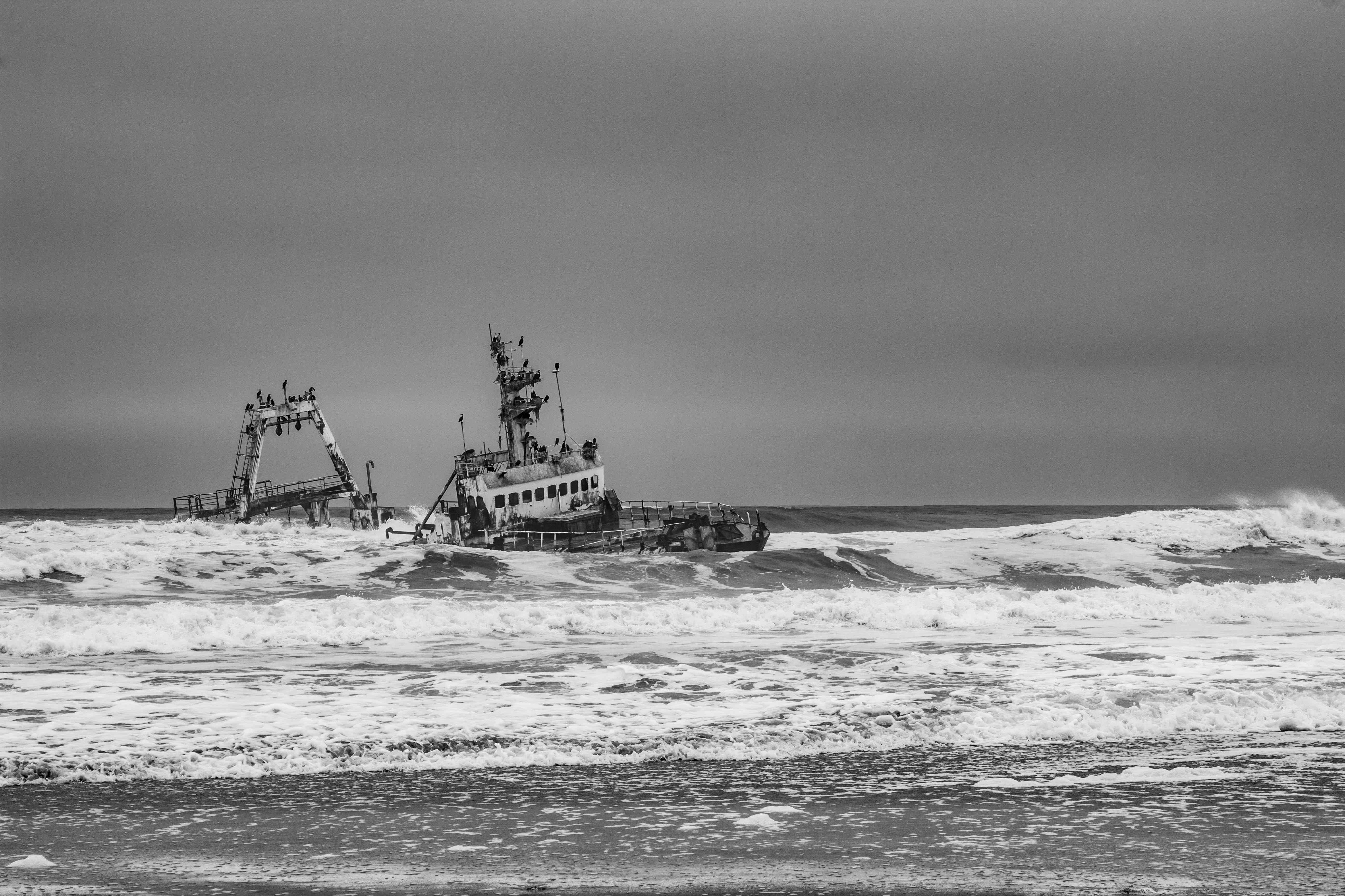 black and white shipwreck in the water on a rough day