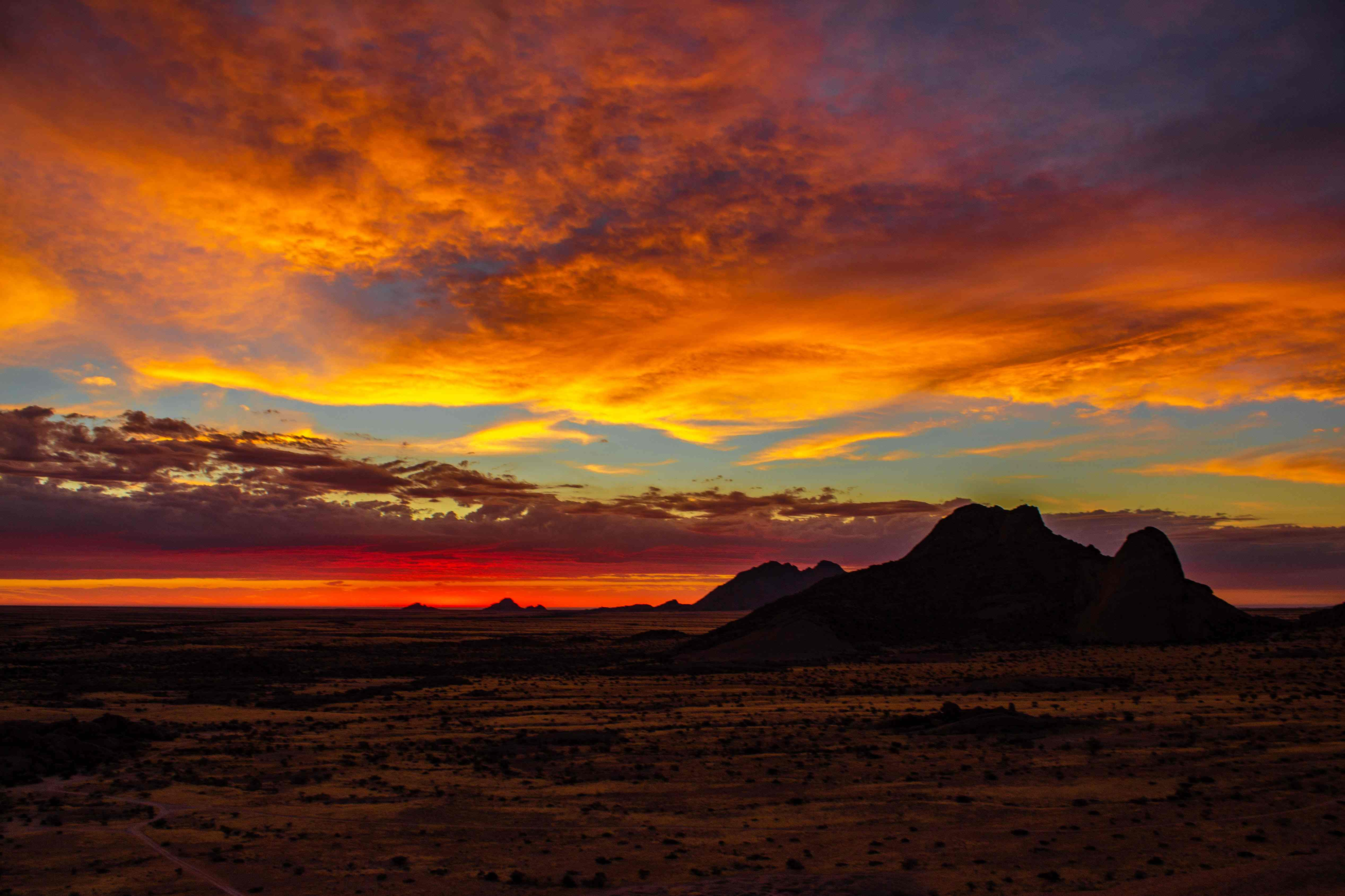 sunset overlooking a mountain; the sky is a combination of bright pinks, purples, blues, and oranges with a hint of yellow