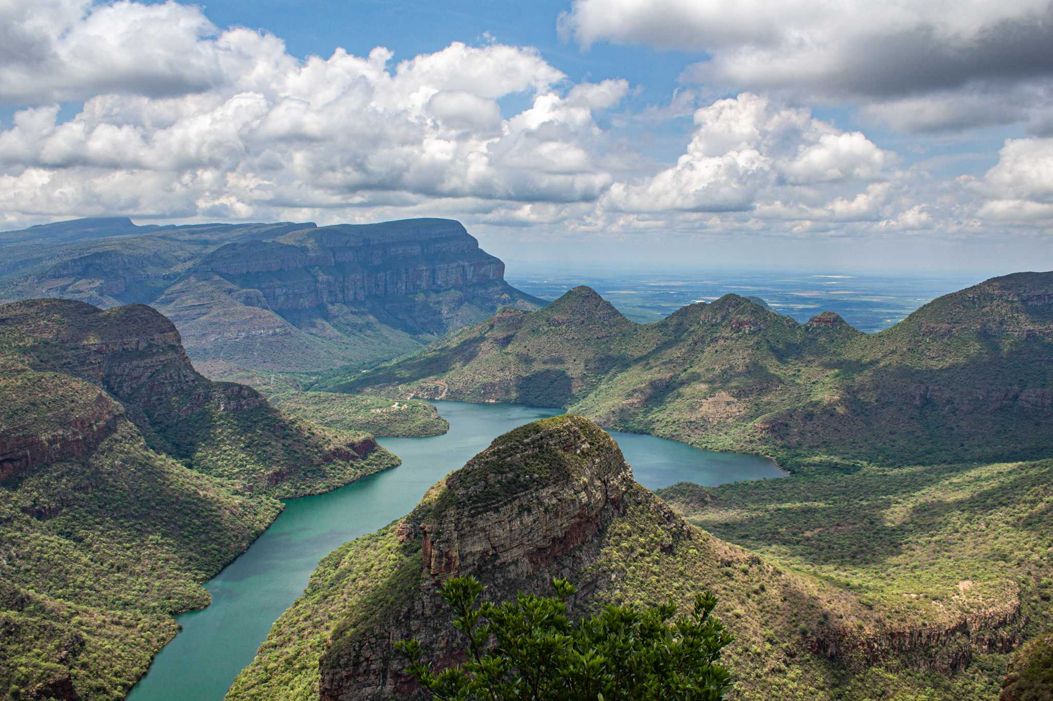 a light blue river cuts through a green, mountainous landscape - a beautiful stop on your south africa vacation