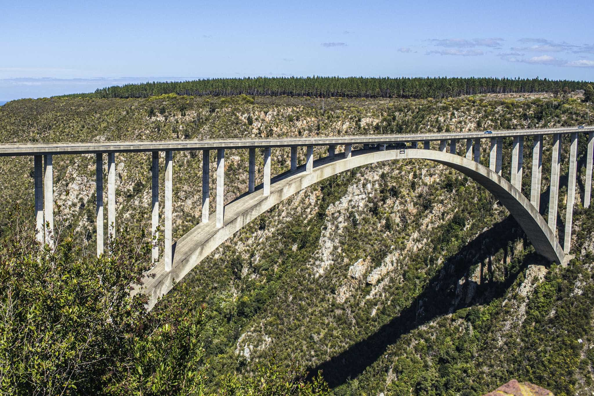 a bridge arches between two canyons; cars drive over it, but under it you can see the platform for the world's highest bungee bridge jump - south africa vacation