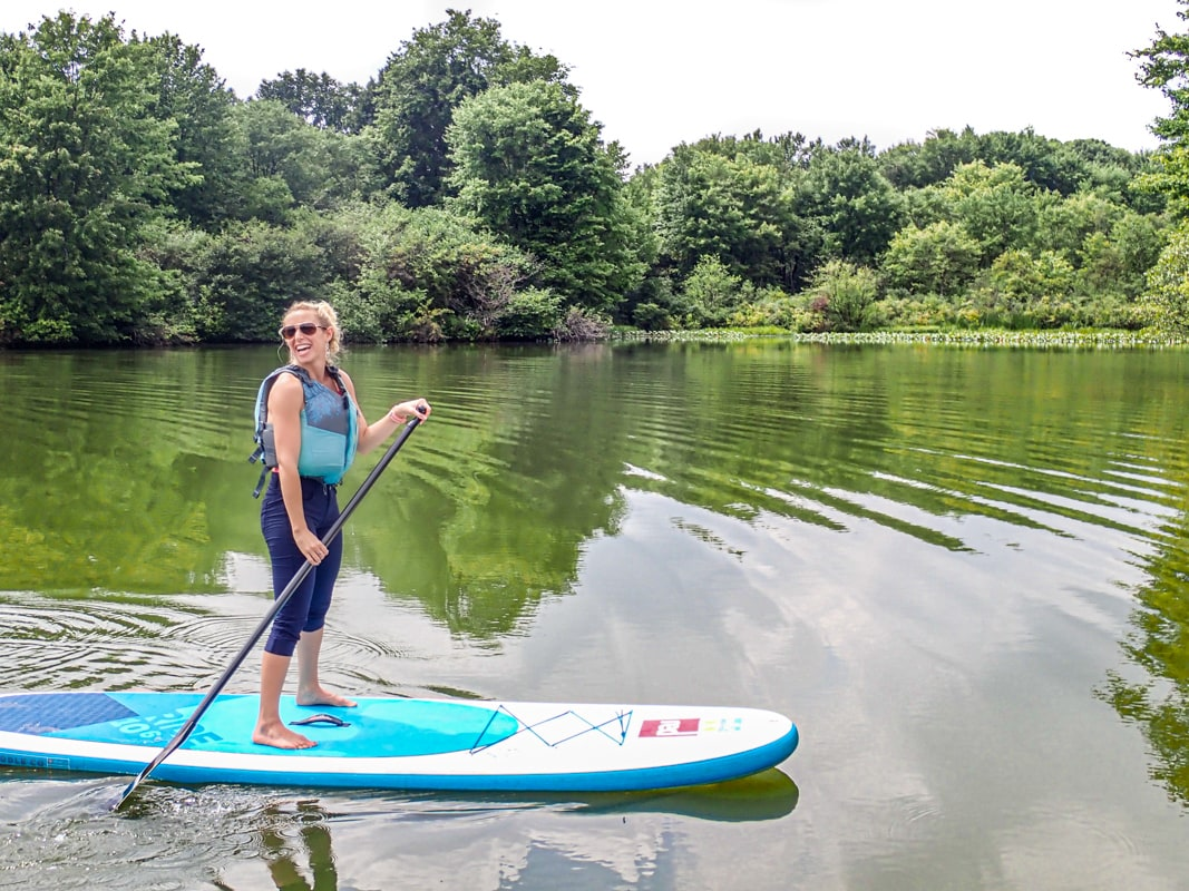 girl stands on paddleboard on a lake with reflections in butler county