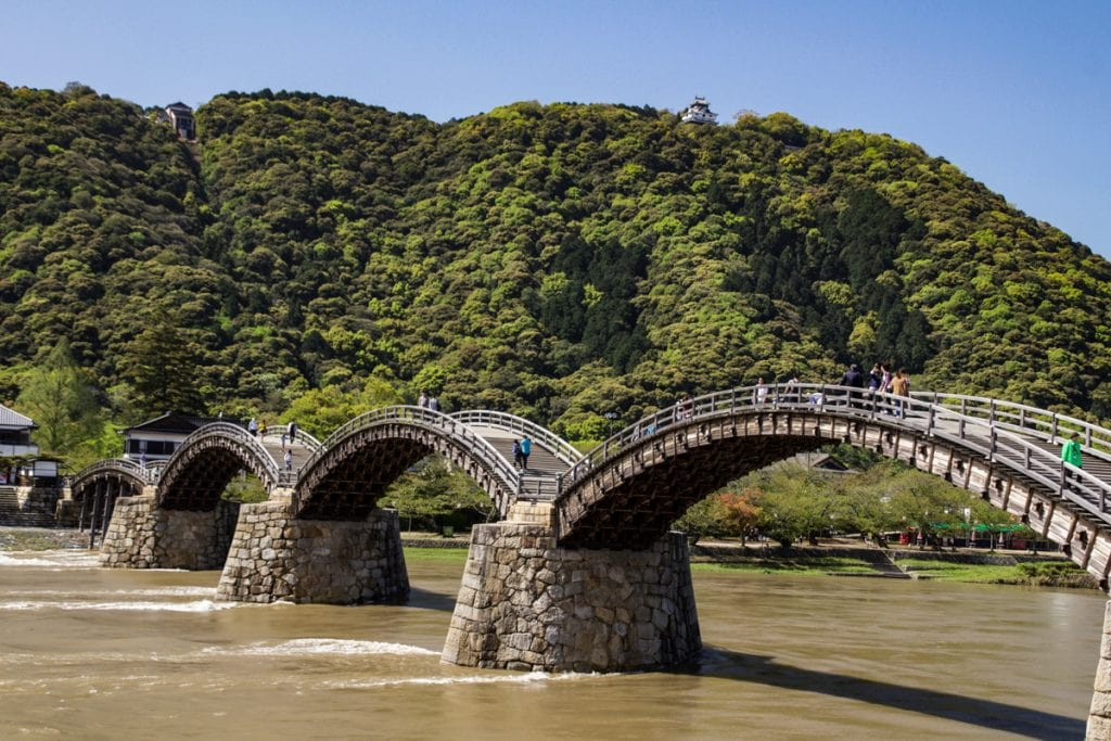 a wooden bridge with four arches in iwakuni - places to visit in japan