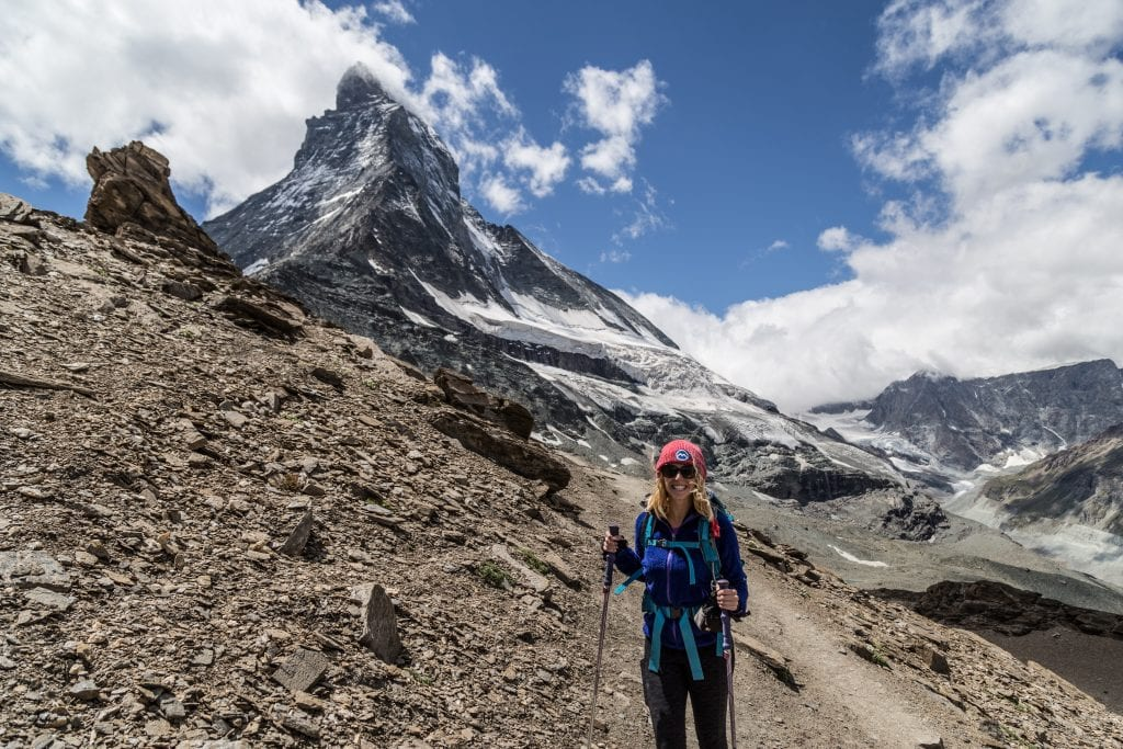 girl with a blue sweatshirt, red hat, and hiking poles stands in front of the matterhorn in switzerland - travel essentials