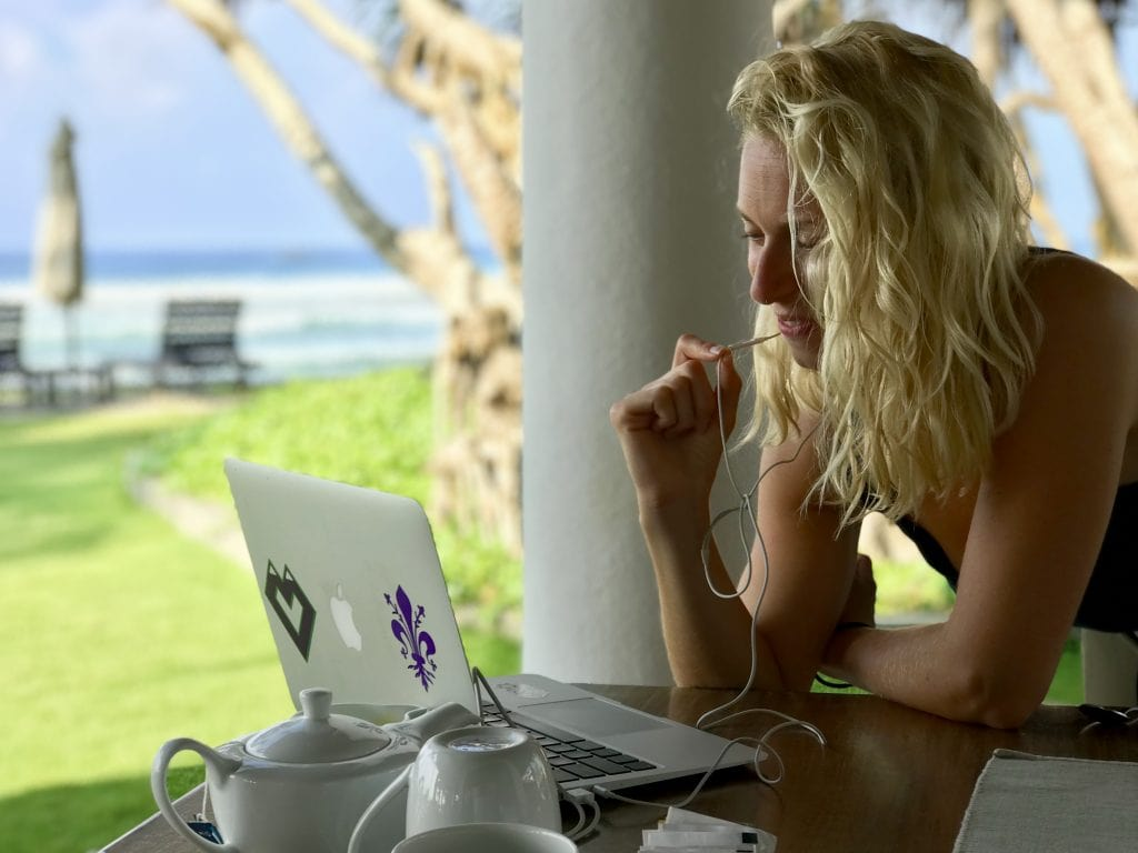 girl on laptop by the ocean - travel essentials