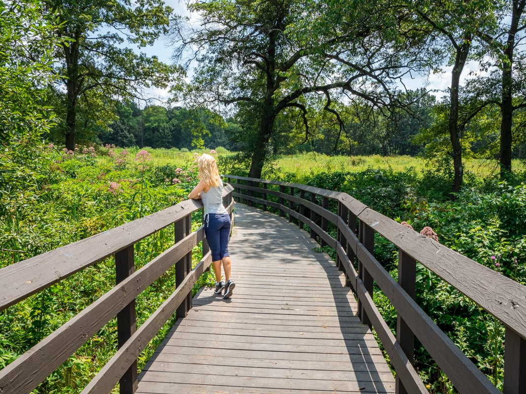 a girl stands on a walkway overlooking a prairie in butler county