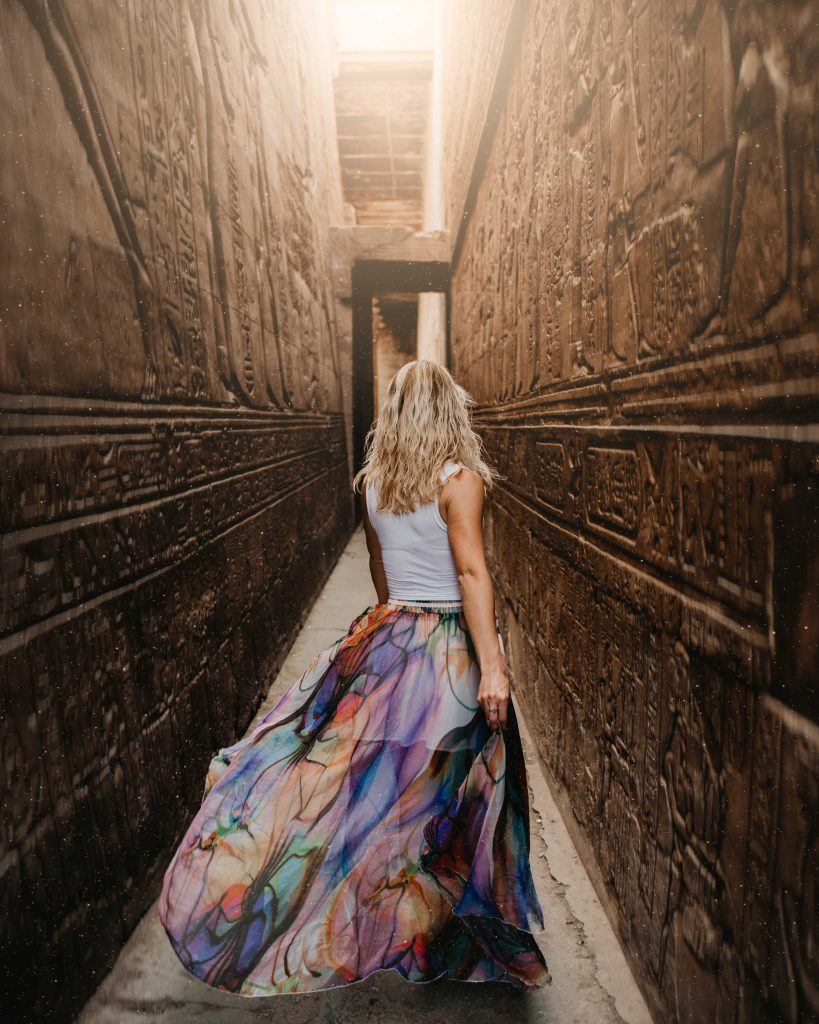 a girl with blonde hair walks through a narrow alleyway surrounded by hieroglyphs on her luxury nile cruise
