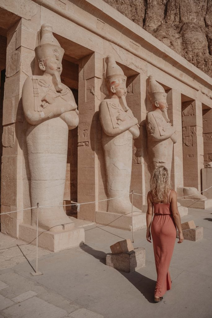 a girl with blonde hair in a rose dress walks through the temple of hateshepsut on her luxury nile cruise