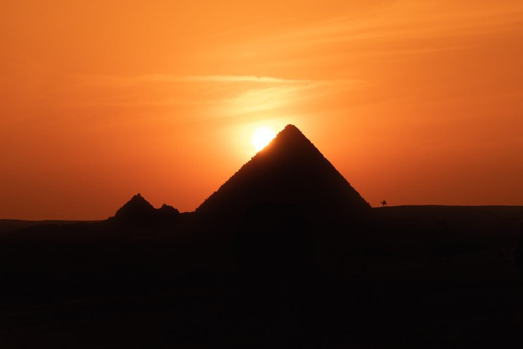 a silhouetted pyramid with sunset and a camel in the distance