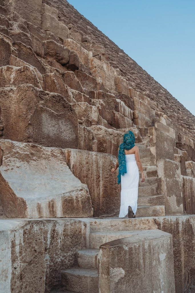 a girl climbs up the great pyramid of giza while visiting the pyramids