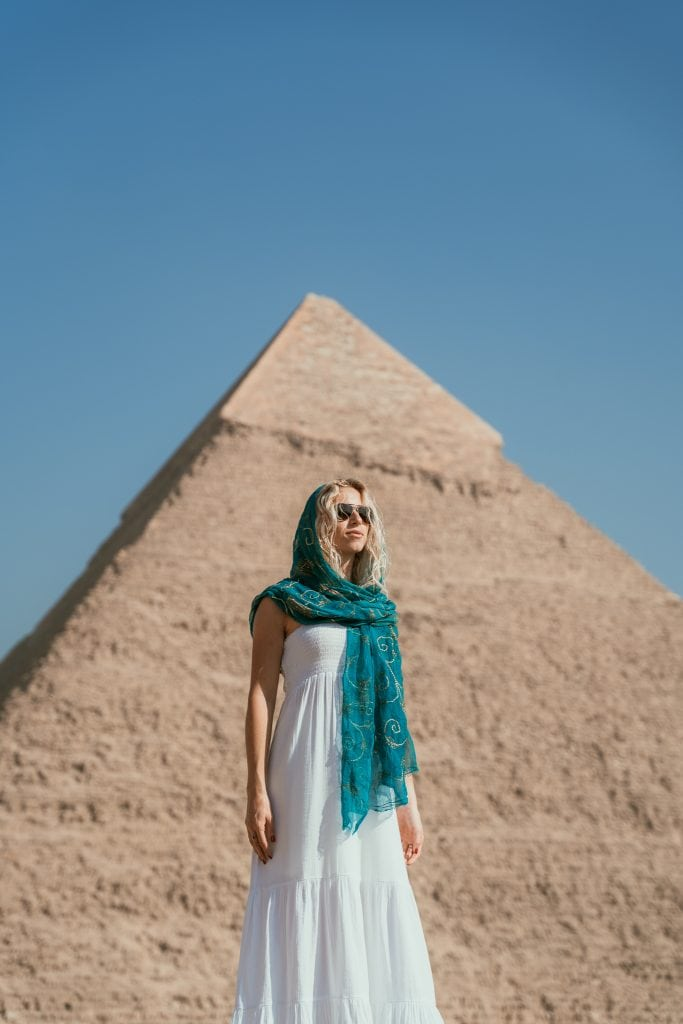 a girl stands in front of a pyramid wearing a white dress and blue headscarf on her egypt pyramids tour